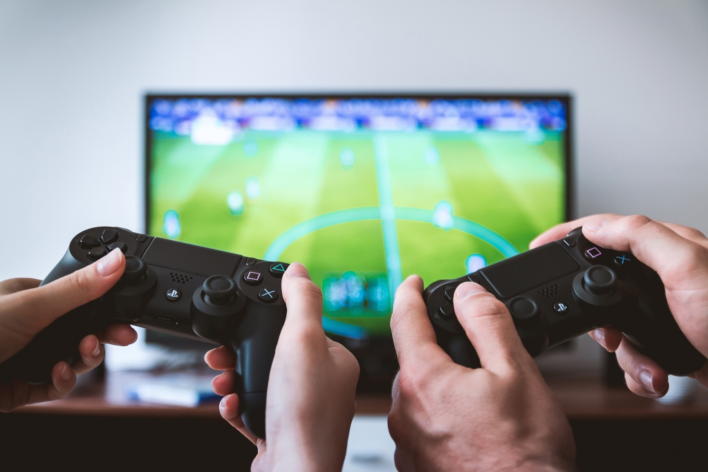 Foto av to personer som holder PS4-kontrollere foran en TV med et fotballspill
