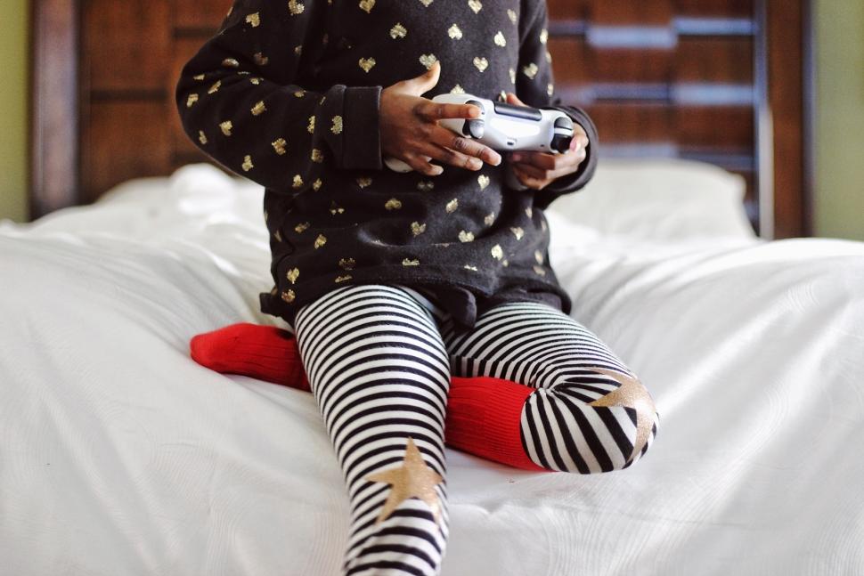 Foto av et barn i en seng som holder en spillkontroll