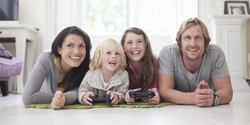 Glad familie som spiller spill sammen.